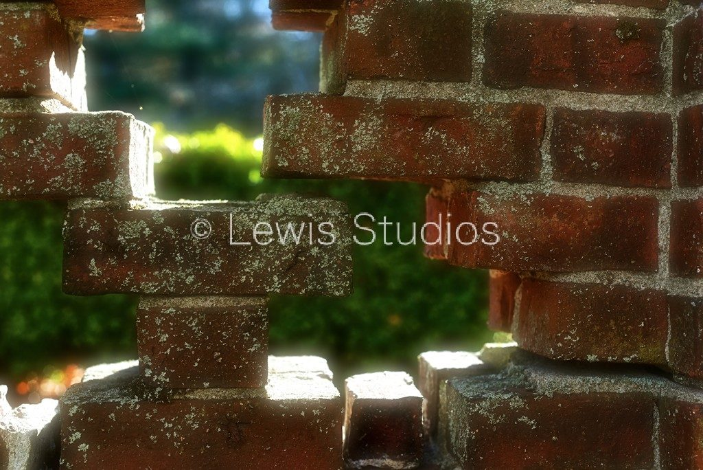 Image of opening in brick wall around gardens